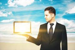 Man holding blank laptop at beach Stock Photo