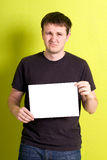 Man holding a blank paper. On green background stock photography