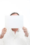 Man holding blank paper in front of his face. Man holding blank white paper with room for your text or message in front of his face Royalty Free Stock Photos