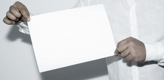 Man holding blank paper on white background. royalty free stock image