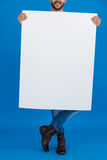 Man holding a blank placard. Against blue background Stock Images