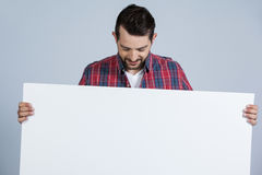 Man holding a blank placard. Against grey background Royalty Free Stock Photos