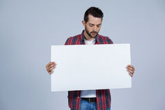 Man holding a blank placard. Against grey background Stock Photos