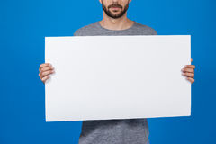 Man holding a blank placard. Close-up of a man holding a blank placard against blue background Royalty Free Stock Photos