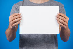 Man holding a blank placard. Close-up of a man holding a blank placard against blue background Stock Photography