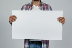 Man holding blank placard. Close-up of man holding a blank placard against grey background Stock Photography