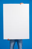 Man holding a blank placard in front of his face. Against blue background Royalty Free Stock Photos