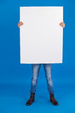 Man holding a blank placard in front of his face. Against blue background Stock Photography