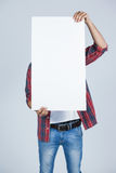 Man holding a blank placard in front of his face. Against white background Royalty Free Stock Photos