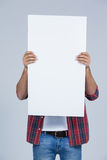 Man holding a blank placard in front of his face. Against white background Royalty Free Stock Images