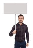 Man holding a blank placard. Man with blank placard looking at camera, white background Royalty Free Stock Photos