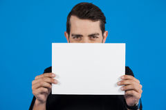 Man holding a blank placard. Portrait of man holding a blank placard against blue background Royalty Free Stock Images