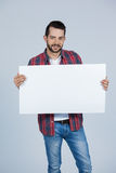 Man holding a blank placard. Portrait of a man holding blank placard against grey background Stock Photo