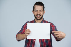 Man holding a blank placard. Portrait of man holding a blank placard against grey background Stock Images