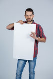 Man holding a blank placard. Portrait of man holding a blank placard against grey background Royalty Free Stock Photo