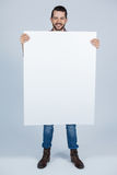 Man holding a blank placard. Portrait of man holding a blank placard against grey background Stock Photography