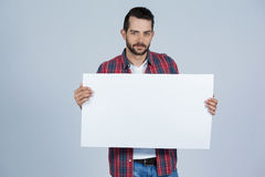 Man holding a blank placard. Portrait of a man holding blank placard against grey background Royalty Free Stock Photos