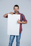 Man holding a blank placard. Portrait of man holding a blank placard against grey background Royalty Free Stock Photography