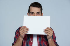 Man holding a blank placard. Portrait of man holding a blank placard against grey background Royalty Free Stock Images
