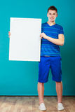 Man holding blank presentation board on blue Royalty Free Stock Photos