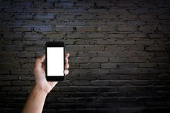 Man holding blank screen of a smartphone at the old black brick Stock Images