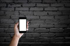 Man holding blank screen of a smartphone at the old black brick Stock Photography