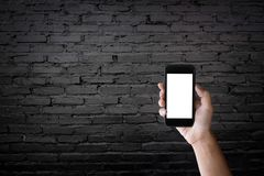 Man holding blank screen of a smartphone at the old black brick Royalty Free Stock Photos