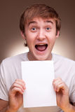 Man Holding blank Sheet. Happy young Man Holding blank Sheet Stock Photography