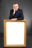 Man holding blank white card in frame. Portrait of a man holding blank white card in frame on a gray background stock images