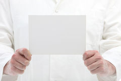 Man holding blank white card in front of himself Royalty Free Stock Images