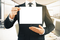 Man holding blank whiteboard. Businessman holding blank white board in interior. Mock up Stock Photo
