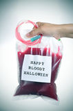 Man holding a blood bag with the text happy bloody halloween, vi Royalty Free Stock Images
