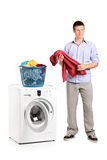 Man holding a blouse and a washing machine Stock Images