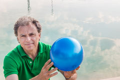 Man holding blue ball Royalty Free Stock Photography