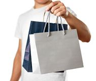 Man holding a blue and grey gift bags. Close up. Isolated on white background stock image
