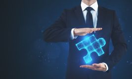 Man holding blue puzzle. Man holding glowing blue puzzle on blurry background. Future and innovation concept Stock Photography