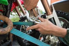 Man holding blue tie-down strap buckle that is used to secure mo. Man holding heavy duty blue tie-down strap buckle that is used to secure dirt bike to a trailer royalty free stock photos
