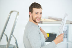 Man holding blueprint for assembling furniture Royalty Free Stock Photo