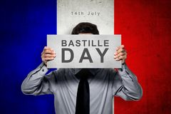 Man holding board with bastille day message. Over france color flag background stock photo