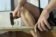 Man Holding Board while Hammering - Horizontal Royalty Free Stock Images