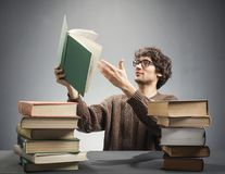 Man holding a book, making a discovery. Man lifting a book from the table, pointing his hand on a page. Making a discovery. Nerd concept Stock Images