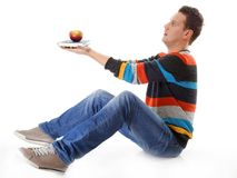 Man holding a book and one red apple full body Stock Photo