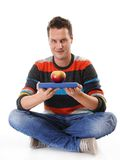 Man holding a book and one red apple full body Stock Photos