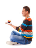 Man holding book and red apple. Healthy diet. Royalty Free Stock Photos