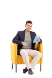Man holding a book seated in an armchair Royalty Free Stock Image
