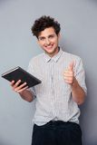 Man holding book and showing thumb up. Happy young man holding book and showing thumb up over gray background Royalty Free Stock Photography