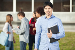 Man Holding Book With Students In Background On Stock Photography