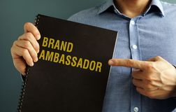 Man holding book with title Brand Ambassador. royalty free stock image