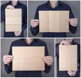 A man holding booklet. A man in a blue shirt holding a blank booklet royalty free stock images