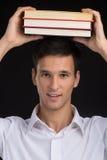 Man holding books on black background. Stock Images